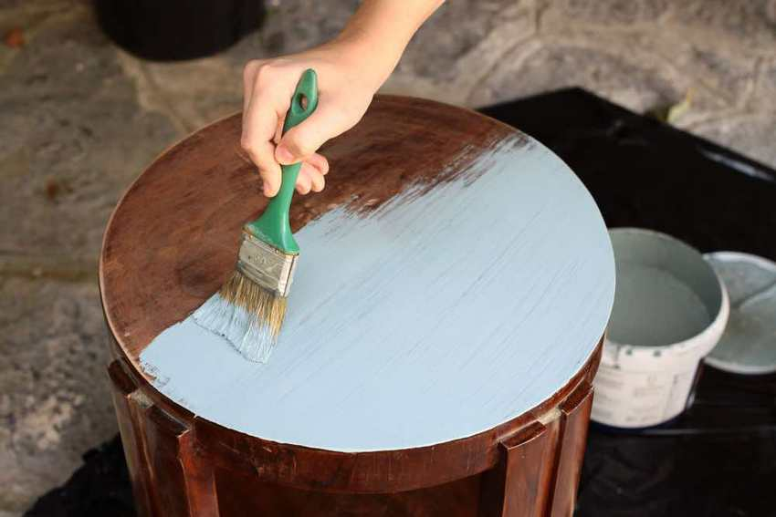Closeup of person painting over stain on a small, round table.