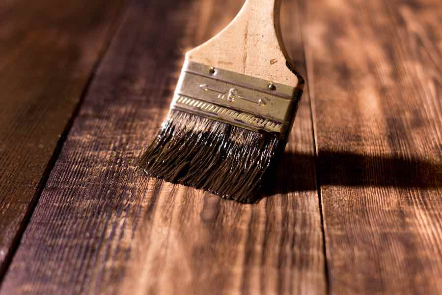 Brush applying stain on wood