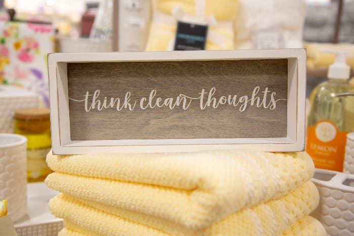 """Rustic farmhouse bathroom sign with """"think clean  thoughts"""" in white lettering, placed on stack of pale yellow towels with out of focus bathroom in the background."""