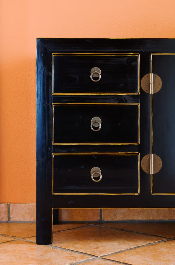 A partial view of a dark wooden dresser with thin gold lines painted around the edge of the front of the drawer faces and door along the openings for the drawers and door.