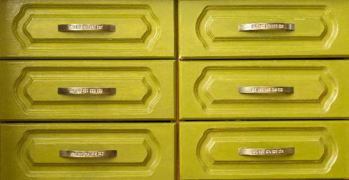 Closeup of a yellow green painted dresser with carved panel drawers and metal hardware.