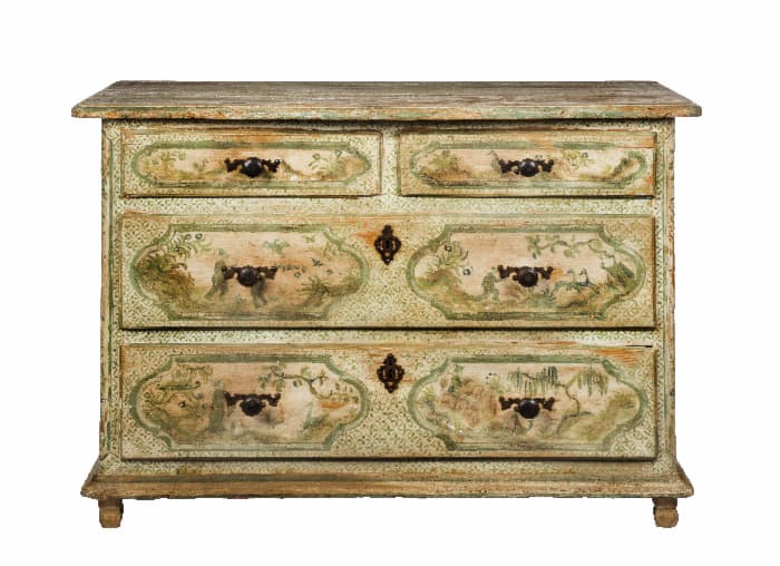 A painted dresser with painted tree murals on the fronts of the drawers.