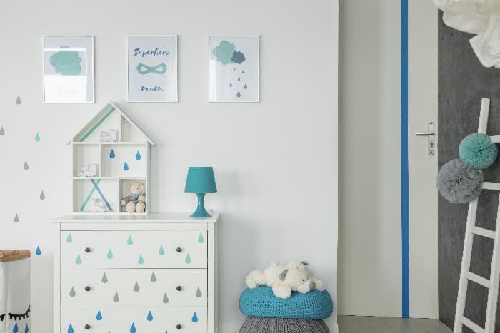 A child's room with a white painted dresser with raindrop stencils on the drawers.
