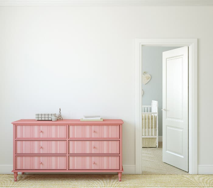 A painted dresser with a pink monochromatic pattern of vertical stripes  the drawers.
