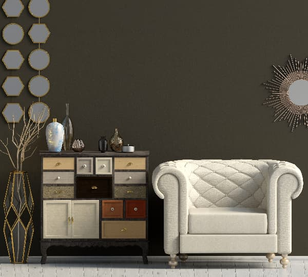 A painted dresser with drawers painted in different colors next to a white upholstered chair, against a dark wall.
