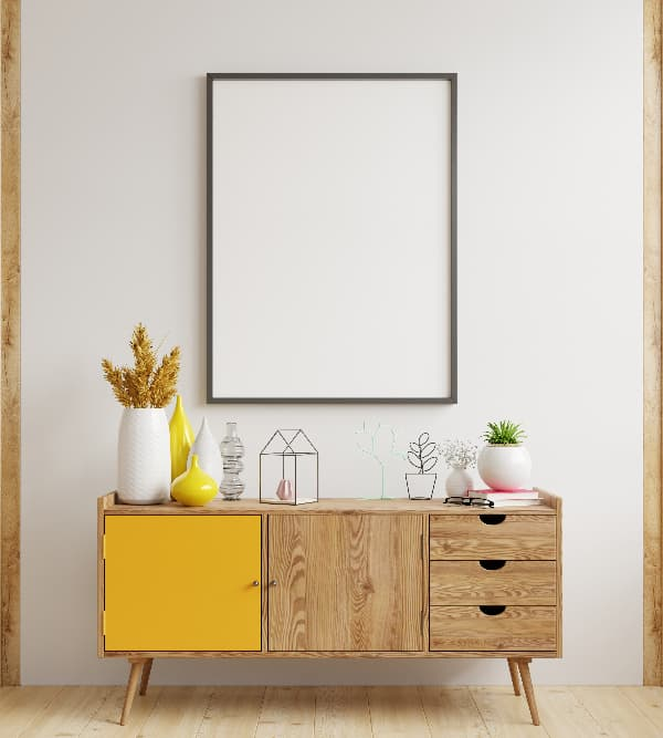 A wooden dresser with a single door painted golden yellow.