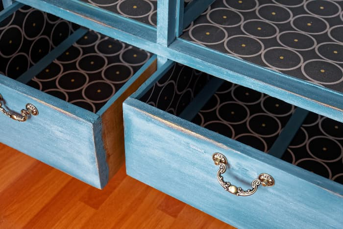 Closeup of two open drawers in a blue painted dresser with antique distressing.