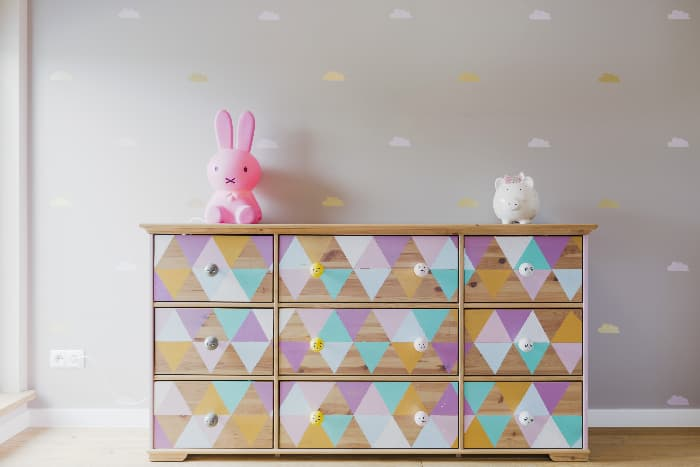 A painted dresser with a pop art diamond pattern of lilac, lavender, aqua, gold, and wood grain triangles, a pink rabbit and a white ceramic piggy bank on top of the dresser, against a pale lavender wall.
