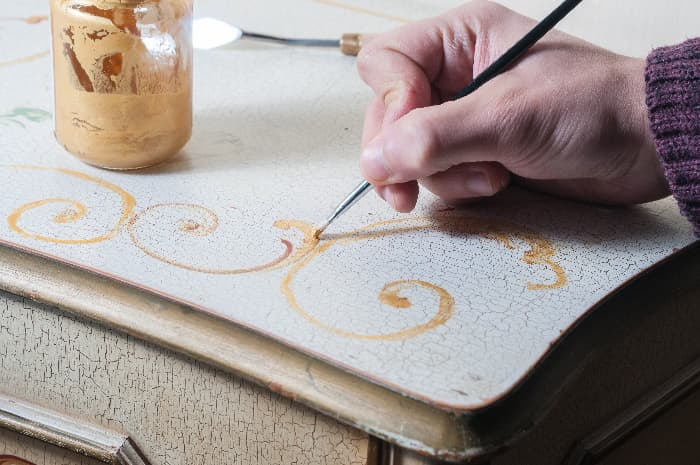 A closeup of a hand painting a gold curlicue design in the corner on the top of a white painted dresser.