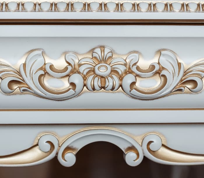 Closeup of gold paint-highlighted ornate detailing on a white painted dresser.