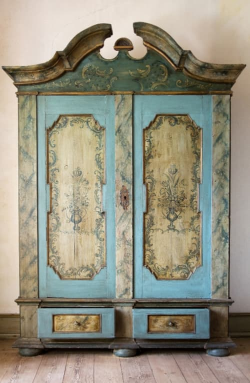 A ornate armoire with blue paint and subtle blue floral designs painted on inlaid panels on the doors and the drawers.