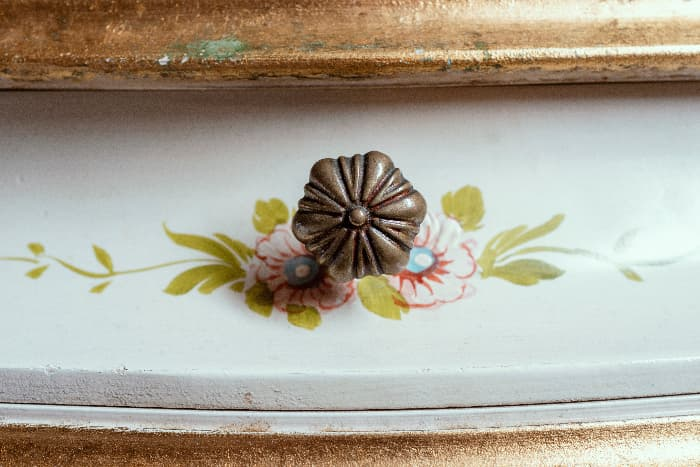 A closeup of stenciled floral elements behind a decorative floral motif knob on a white painted dresser drawer.