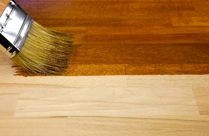 Closeup of paintbrush applying stain to wood.