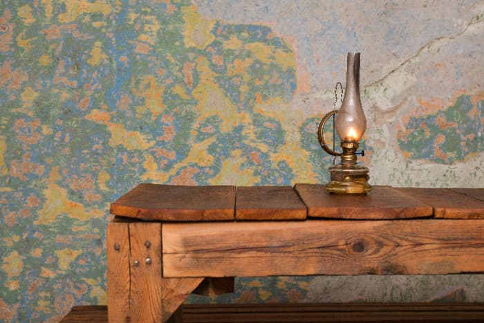 Medium-stain table made of warped planks against wall with peeling wallpaper.