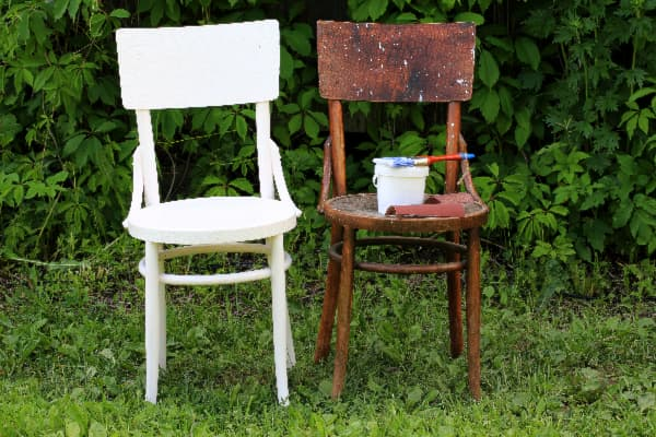 White painted chair next to a wood-stained chair -- example of how to paint over stain.