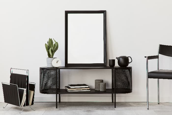 Black furniture decor -- chair, magazine stand, side table, and mirror.