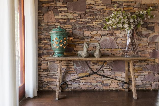 Rustic wooden table with ironwork elements serving as a farmhouse desk.