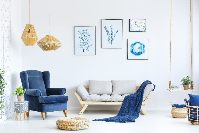 A blue furniture accent piece -- a blue armchair in a white living room that ties in various smaller blue items and blue artwork on the walls.