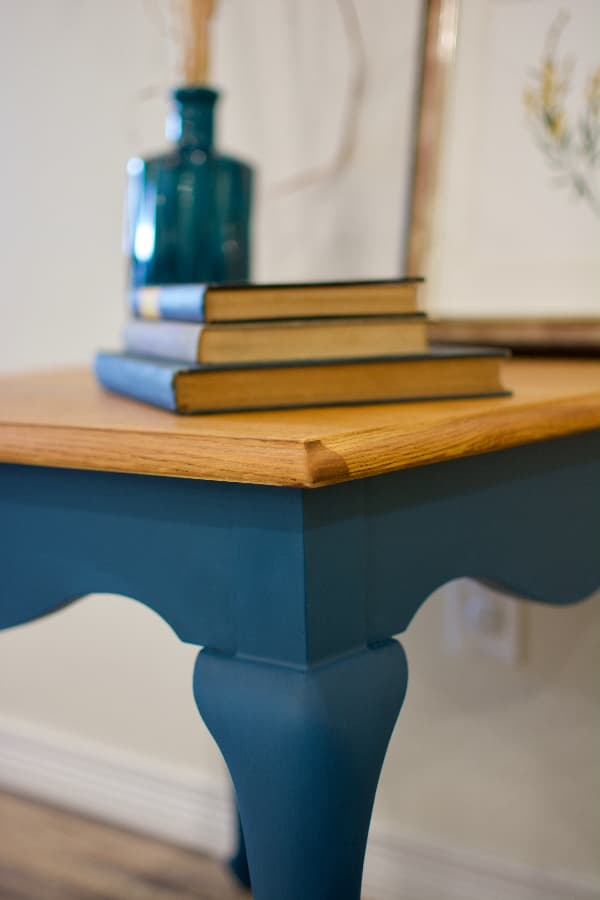 Closeup of a corner leg of an end table painted navy blue -- a piece of blue furniture with a classic, timeless feel to it.