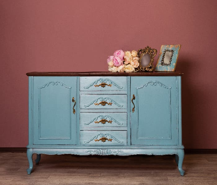 An antique dresser painted light blue against a dark rose wall -- a blue furniture statement piece for the room.