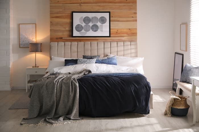 A bedroom with a blue comforter/bedspread, along with various blue accessories -- bedding and accessories can be a decorating alternative to blue furniture pieces.