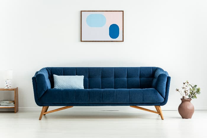 A modern style sofa in navy blue fabric in a white living room with a piece of blue abstract art hung above the sofa -- an example of understate and elegant blue furniture.