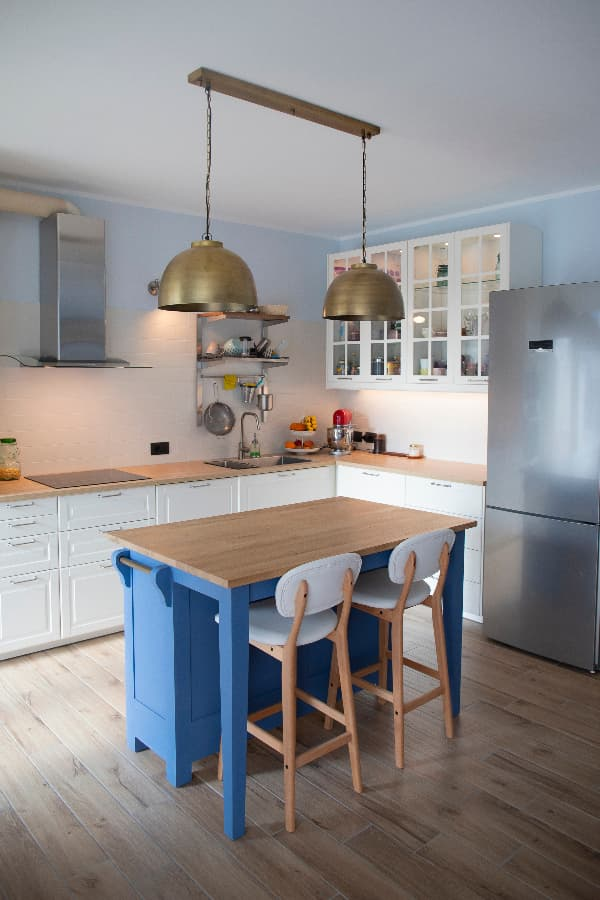 A white kitchen with butcher block counters, glass front cabinets, and stainless appliances with a kitchen island painted a primary blue color -- a blue island brings blue furniture into the kitchen.