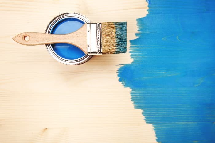 Paintbrush with blue paint or stain sitting on can with plywood background,