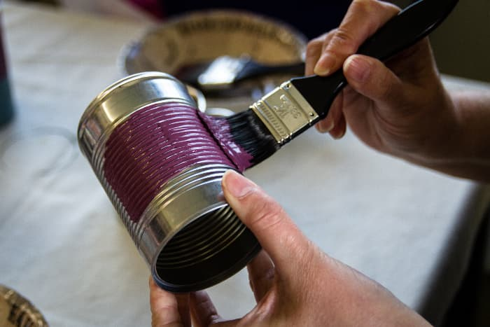Closeup of hands painting purple chalk paint onto a metal can.