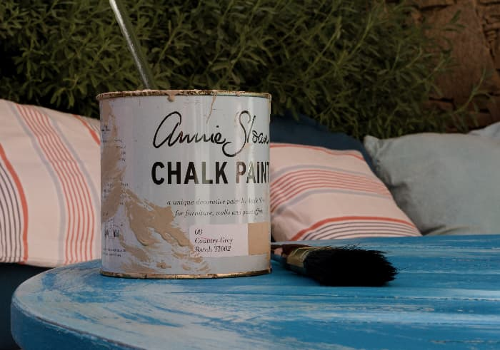 Can of Annie Sloan brand Chalk Paint on distressed blue painted table with striped pillows in the background.