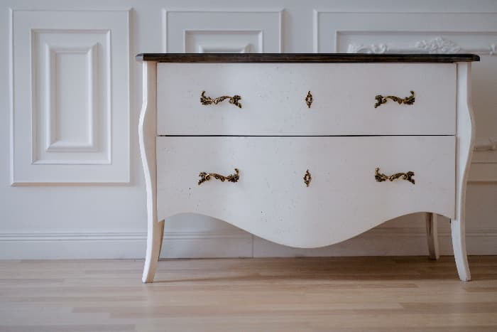 White painted dresser with black top, brass hardware and curved lines against a white wall and light wood flooring.