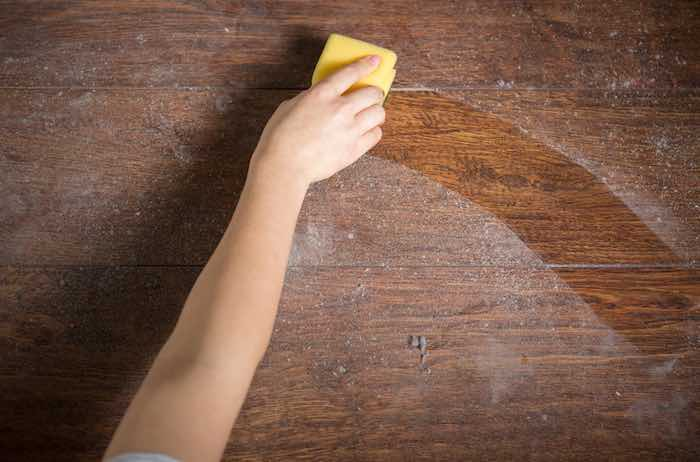 Cleaning dusty wood furniture with a yellow sponge.