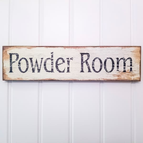 """Closeup of an antique farmhouse sign reading """"Powder Room"""" hung on a white paneled wall."""