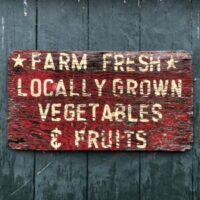Red Farmhouse Sign advertising farm produce in white letters against blue gray plank wall.