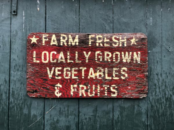 A weathered red farmhouse sign advertising farm produce in white letters hung on a blue-gray plank wall.