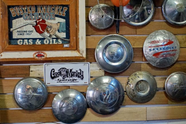 A collection of old hubcaps and garage artwork hung on a rustic wooden wall -- a creative example of farmhouse signs