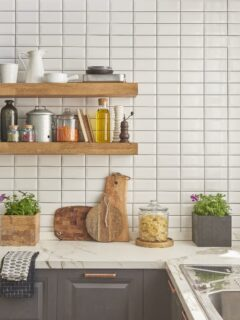 White tiled kitchen accent wall with light brown floating shelves holding kitchen items.