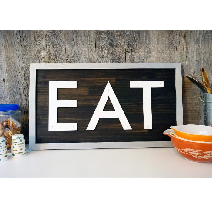 """A metal-framed farmhouse kitchen sign with the word """"EAT"""" in bold white letters on a dark wooden background.  The sign is on a white counter top propped against a rustic wooden plank wall."""
