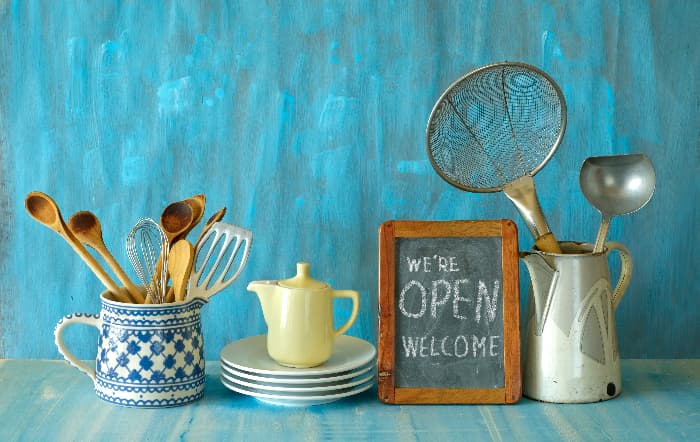 """A small chalkboard farmhouse kitchen sign reading """"We're OPEN"""" and """"WELCOME"""" on the second line.  The sign is on a blue counter next to a stack of white dishes with a small stoneware pitcher on it, along with a metal pitcher and a blue crock that both contain wooden spoons, spatulas, a ladle, and a strainer."""