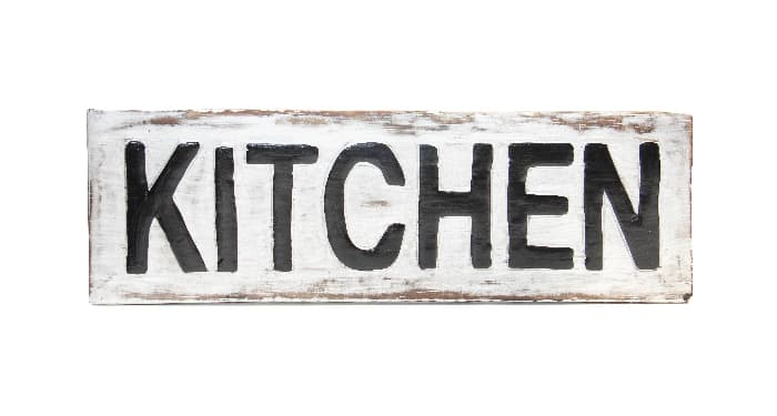 """A rustic wooden farmhouse kitchen sign with distressed white paint and """"KITCHEN"""" in dark, bold lettering."""