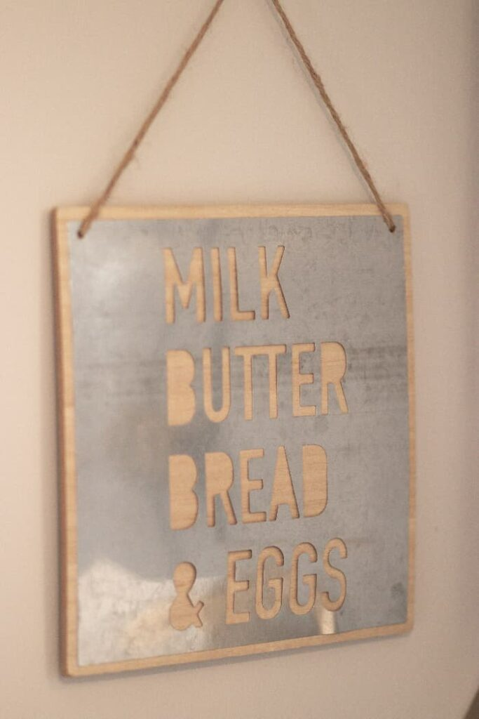 """A metal farmhouse sign that reads """"MILK BUTTER BREAD & EGGS"""" that are cut into the surface of the sign."""
