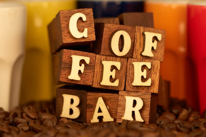 """A farmhouse kitchen sign created by using wooden blocks to spell out """"COFFEE BAR"""" by stacking the blocks on one another."""