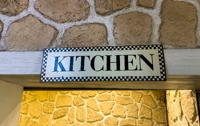 """A farmhouse kitchen sign with black and white checkerboard along the edges with """"KITCHEN"""" in black letters. The sign is hung on a wooden beam in a stone wall."""