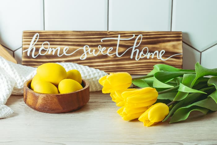 """A wooden plank farmhouse kitchen sign with """"home sweet home"""" in white script lettering.  The sign is propped on a white-washed wooden counter against a white tiled wall, with yellow tulips and a wooden bowl of yellow-colored eggs in front of the sign."""