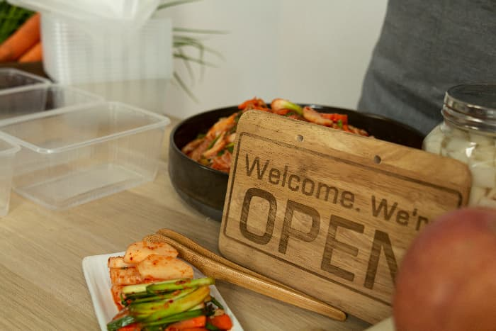 """A modern-style light colored wooden farmhouse kitchen sign with """"Welcome.  We're OPEN"""" in dark brown letters."""
