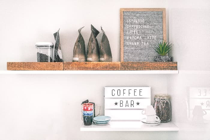 """A white farmhouse sign with """"COFFEE BAR"""" in black letters.  The sign is on a white floating shelf with beneath a longer white floating shelf with various coffee-related items on them."""