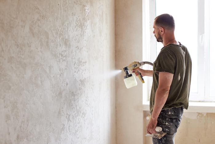 Painter working with a paint sprayer and aiming to prevent blotchy spray paint.