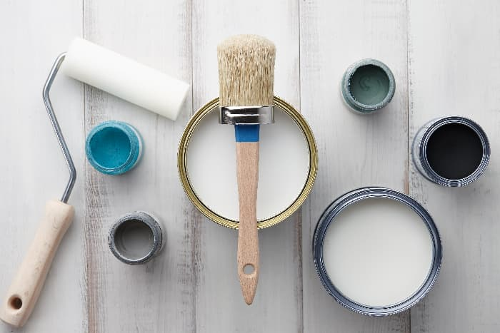 Overhead view of open paint cans (2 large and 4 small), a paint brush, and a paint roller sitting on a whitewashed wooden surface.