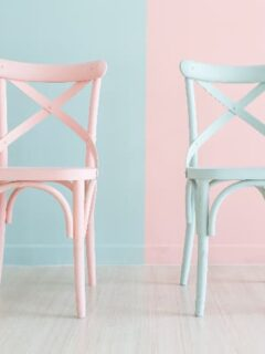 Two painted chairs, one painted pale pink against a pale blue background, the other painted pale blue against a pale pink background