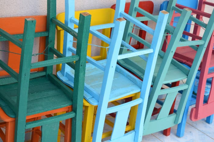 Three upside down painted chairs, each one painted a different shade of blue that demonstrates gradient color painting.